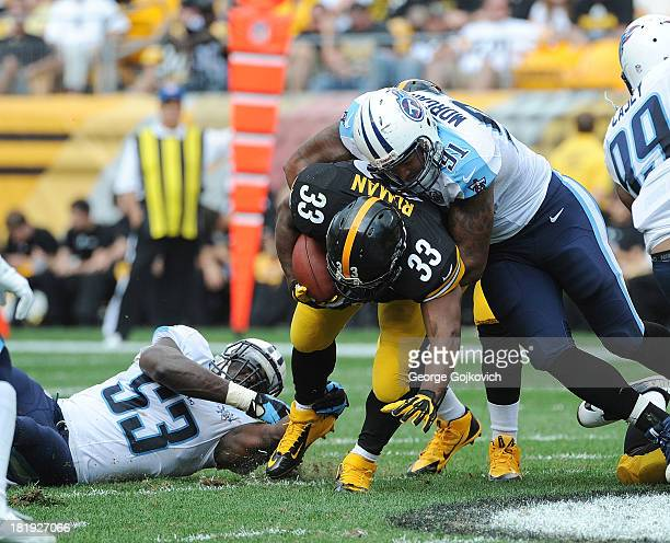 Defensive lineman Derrick Morgan and linebacker Moise Fokou of the Tennessee Titans tackle running back Isaac Redman of the Pittsburgh Steelers at...