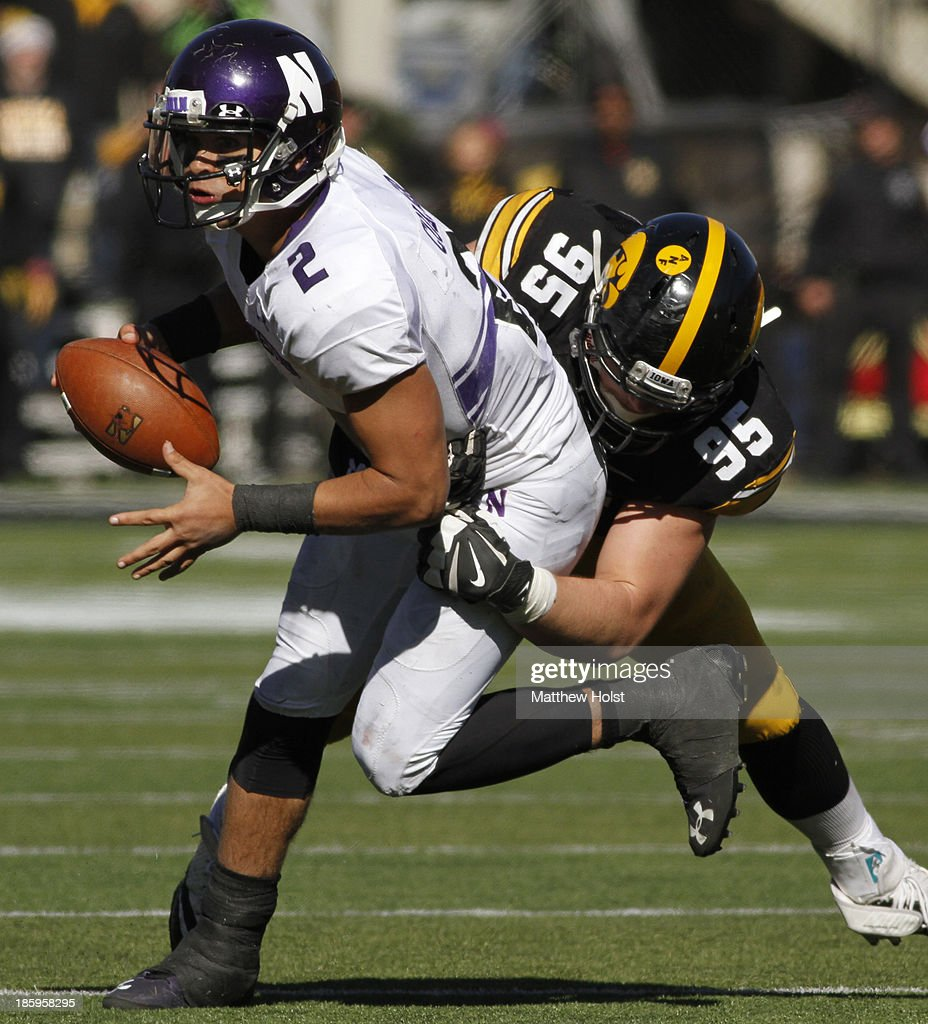 Defensive lineman Drew Ott #95 of the Iowa Hawkeyes makes a sack on quarterback Kain Colter #2 of the Northwestern Wildcats during overtime on October 26, 2013 at Kinnick Stadium in Iowa City, Iowa. Iowa won 17-10.