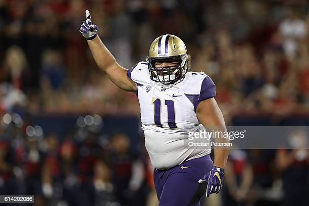 Defensive lineman Elijah Qualls of the Washington Huskies celebrates after a defensive stop against the Arizona Wildcats during the fourth quarter of...