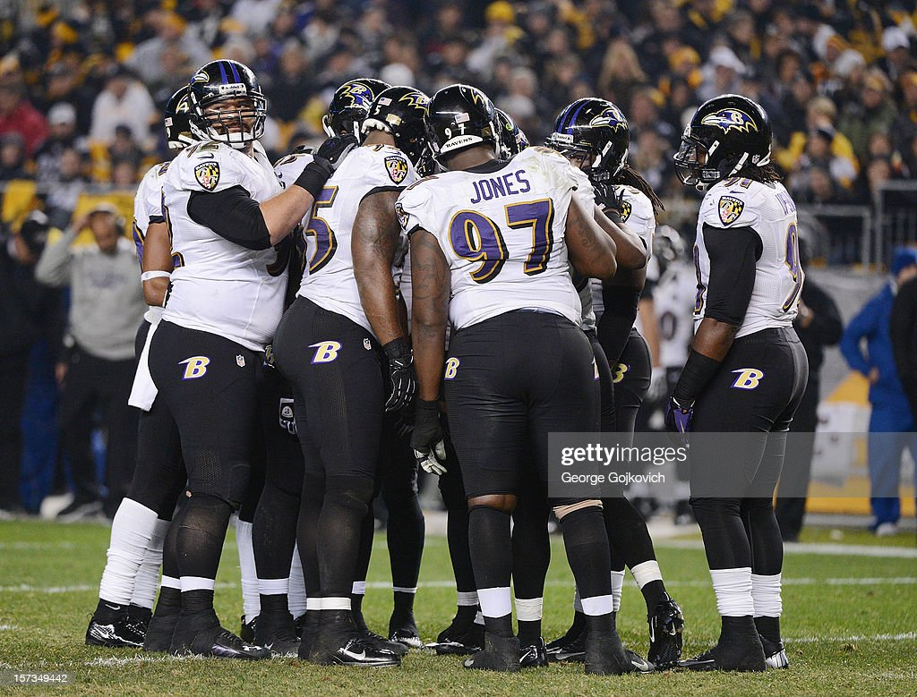 Defensive lineman Haloti Ngata #92 of the Baltimore Ravens looks up as he huddles with other members of the defense, including linebackers Terrell Suggs #55 and Courtney Upshaw #91 and defensive lineman Arthur Jones #97 during a game against the Pittsburgh Steelers at Heinz Field on November 18, 2012 in Pittsburgh, Pennsylvania. The Ravens defeated the Steelers 13-10.