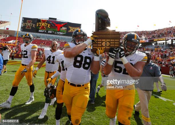 Defensive lineman Jake Hulett of the Iowa Hawkeyes and offensive lineman Boone Myers of the Iowa Hawkeyes celebrate with teammates by carrying the...
