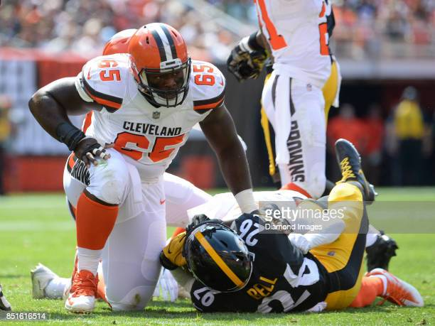 Defensive lineman Larry Ogunjobi of the Cleveland Browns kneels over running back LeVeon Bell of the Pittsburgh Steelers in the second quarter of a...