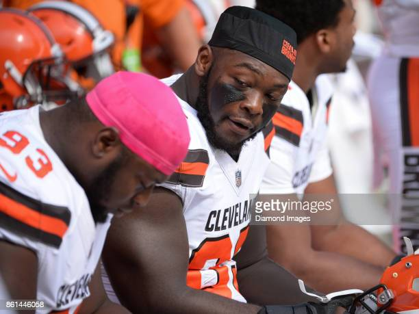 Defensive lineman Larry Ogunjobi of the Cleveland Browns talks with defensive tackle Trevon Coley on the bench prior to a game on October 8 2017...