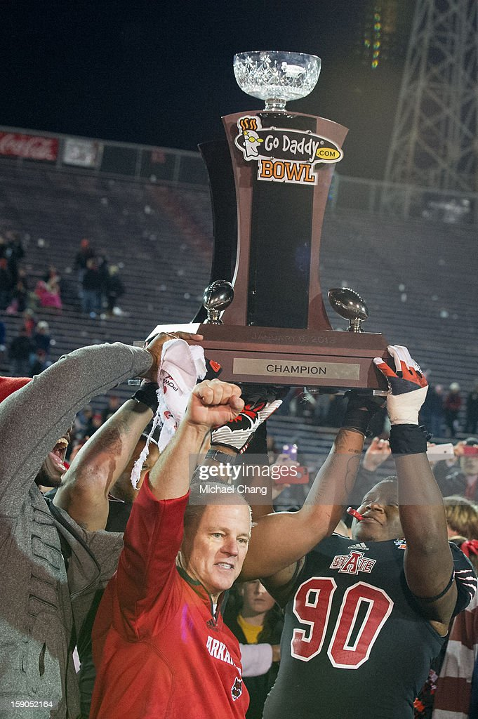 Defensive lineman Ronnell Wright #90 and head coach John Thompson of the Arkansas State Red Wolves celebrate with the GoDaddy.com Bowl trophy on January 6, 2013 at Ladd-Peebles Stadium in Mobile, Alabama. Arkansas State defeated Kent State 17-13.