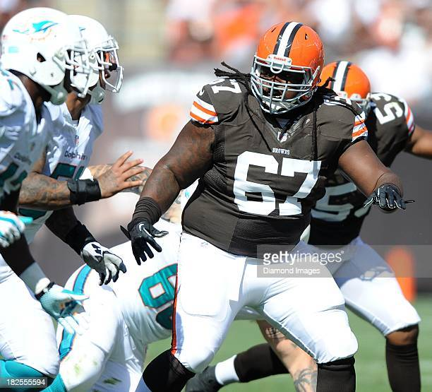 Defensive linemen Ishmaa'ily Kitchen of the Cleveland Browns attempts to get off the block of offensive linemen Mike Pouncey of the Miami Dolphins...