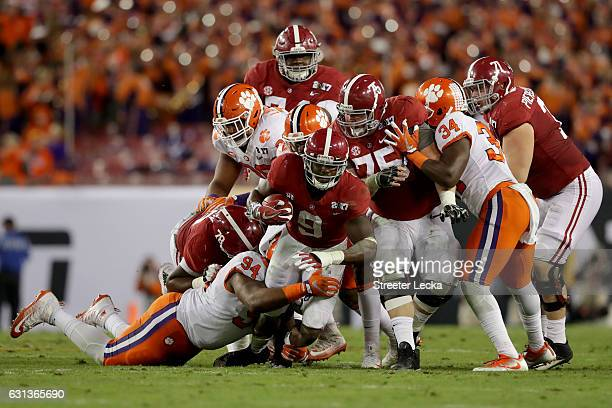 Defensive tackle Carlos Watkins of the Clemson Tigers tackles running back Bo Scarbrough of the Alabama Crimson Tide during the first half of the...