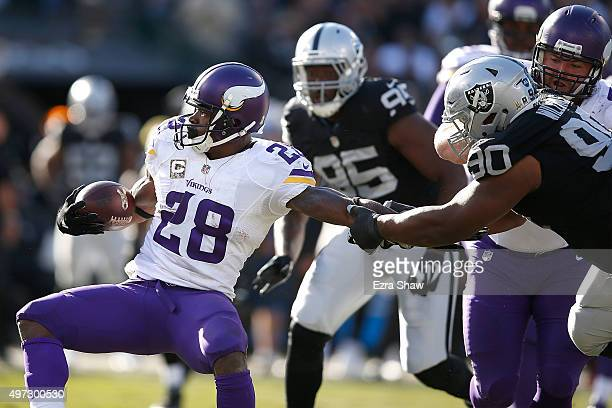 Defensive tackle Dan Williams of the Oakland Raiders attempts to stop running back Adrian Peterson of the Minnesota Vikings in the second quarter at...