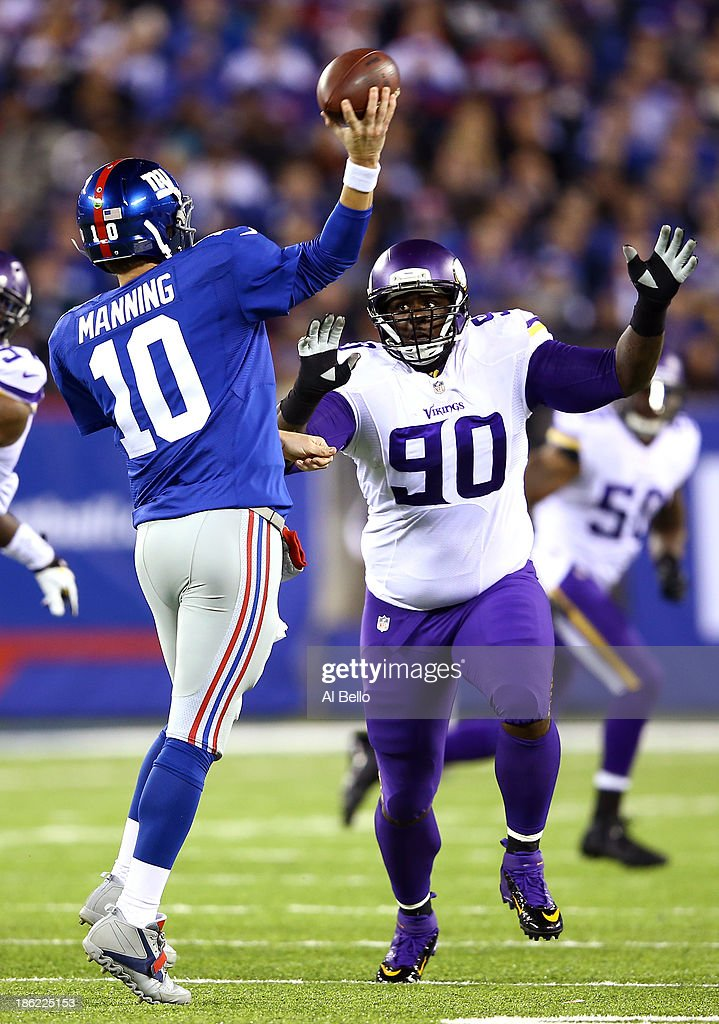 Defensive tackle Fred Evans #90 of the Minnesota Vikings pressures quarterback Eli Manning #10 of the New York Giants during a game at MetLife Stadium on October 21, 2013 in East Rutherford, New Jersey.