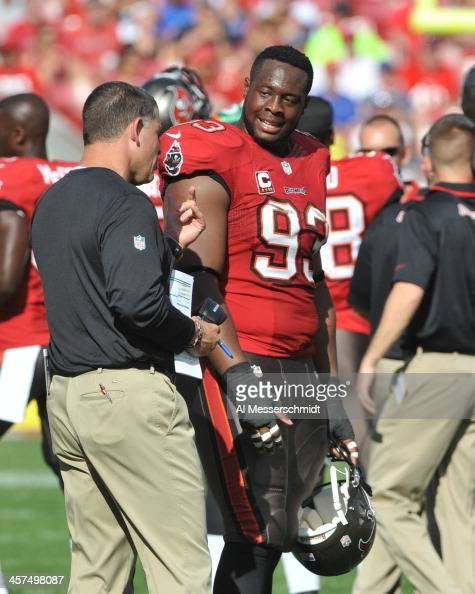 Defensive tackle Gerald McCoy talks with coach Greg Schiano of the Tampa Bay Buccaneers during play against the Buffalo Bills December 8 2013 at...