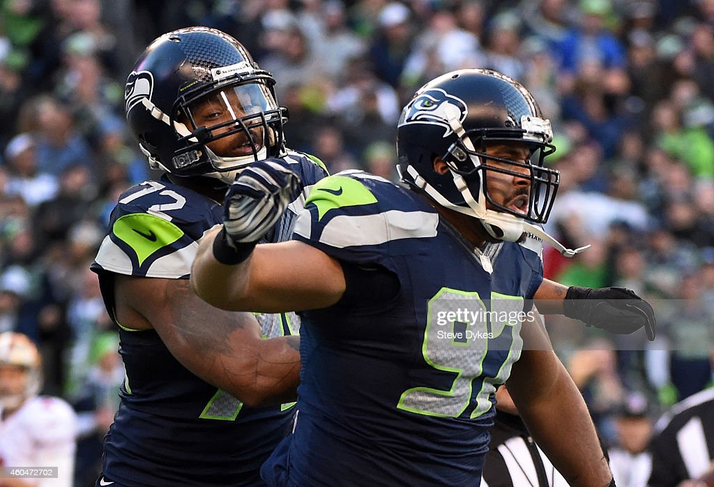Defensive tackle <a gi-track='captionPersonalityLinkClicked' href=/galleries/search?phrase=Jordan+Hill+-+American+Football+Player&family=editorial&specificpeople=13503545 ng-click='$event.stopPropagation()'>Jordan Hill</a> #97 of the Seattle Seahawks celebrates with defensive end <a gi-track='captionPersonalityLinkClicked' href=/galleries/search?phrase=Michael+Bennett+-+American+Football+Defensive+End+-+Born+1985&family=editorial&specificpeople=11360119 ng-click='$event.stopPropagation()'>Michael Bennett</a> #72 of the Seattle Seahawks after making a sack during the third quarter of the game against the San Francisco 49ers at CenturyLink Field on December 14, 2014 in Seattle, Washington.