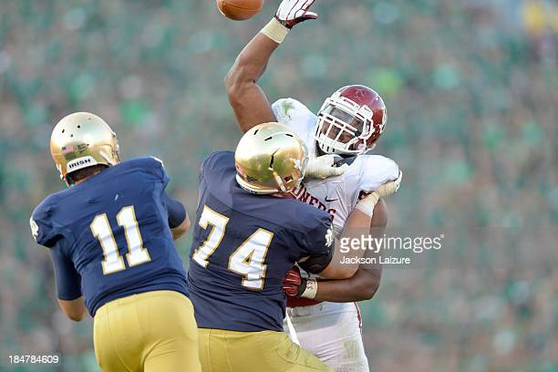 Defensive tackle Jordan Phillips of the Oklahoma Sooners tries to block a pass from quarterback Tommy Rees while being blocked by lineman Christian...