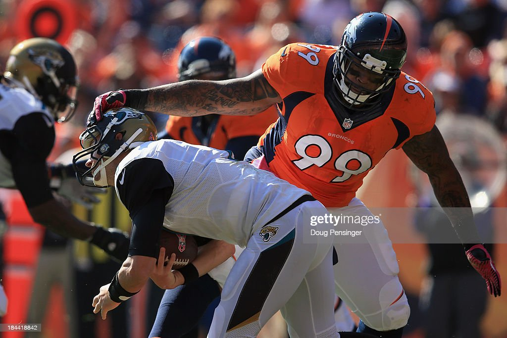 Defensive tackle Kevin Vickerson of the Denver Broncos gets a hand on quarterback Chad Henne of the Jacksonville Jaguars as he scrambles at Sports...