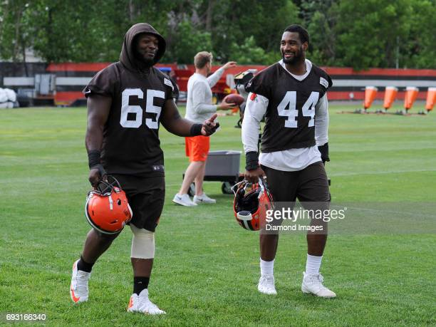 Defensive tackle Larry Ogunjobi and linebacker Nate Orchard of the Cleveland Browns talk as they walk off the field after an OTA practice on June 6...