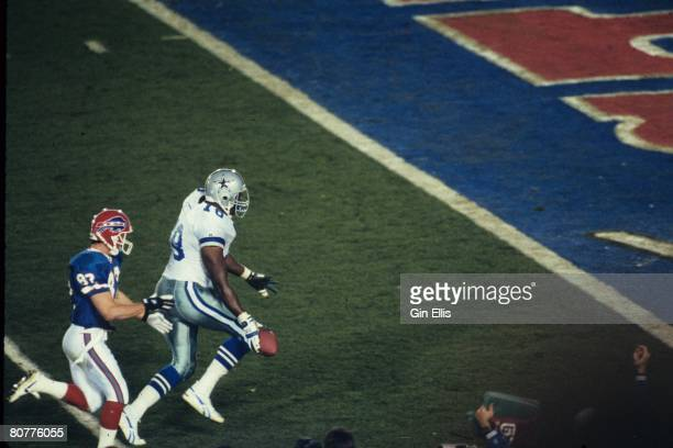 Defensive tackle Leon Lett of the Dallas Cowboys is headed to the endzone with a fumble recovery as wide receiver Don Beebe of the Buffalo Bills...