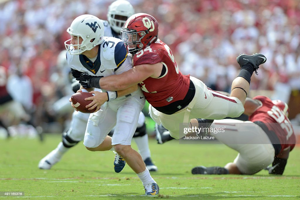 Defensive tackle Matt Dimon of the Oklahoma Sooners leaps and strips the ball from quarterback Skyler Howard of the West Virginia Mountaineers on...