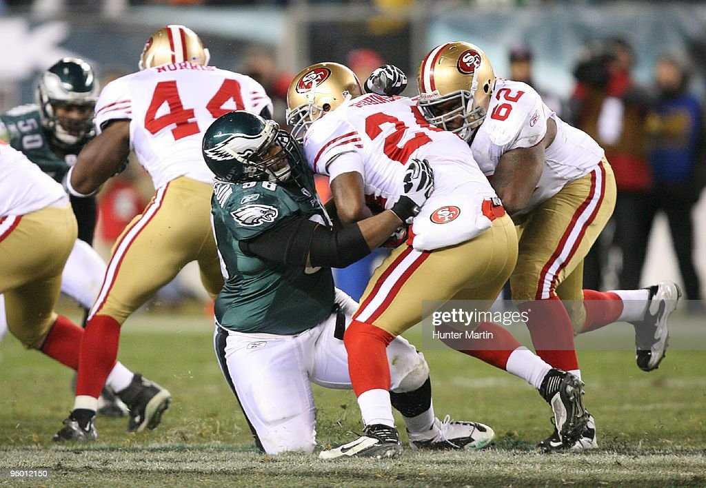 Defensive tackle Mike Patterson of the Philadelphia Eagles tackles running back Michael Robinson of the San Francisco 49ers during a game on December...