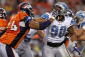 Defensive tackle Ndamukong Suh of the Detroit Lions battles the blocking of offensive tackle Ryan Harris of the Denver Broncos during preseason NFL...
