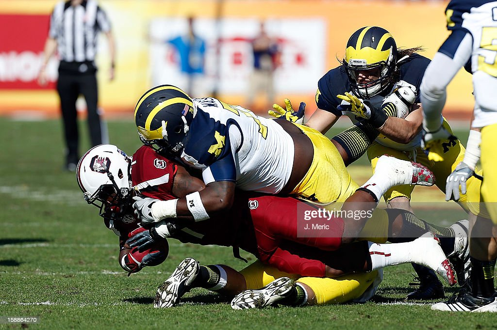 Defensive tackle Quinton Washington #76 of the Michigan Wolverines tackles running back Shon Carson #7 of the South Carolina Gamecocks during the Outback Bowl Game at Raymond James Stadium on January 1, 2013 in Tampa, Florida.