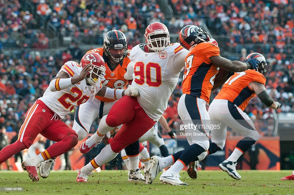 Defensive tackle Shaun Smith #90 of the Kansas City Chiefs tackles running back Knowshon Moreno #27 of the Denver Broncos during a game at Sports Authority Field Field at Mile High on December 30, 2012 in Denver, Colorado.
