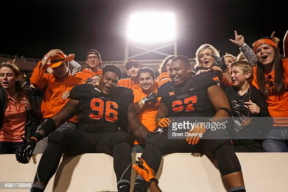Defensive tackle Vincent Taylor and defensive tackle Eric Davis of the Oklahoma State Cowboys celebrate with the fans in the stands after the game...