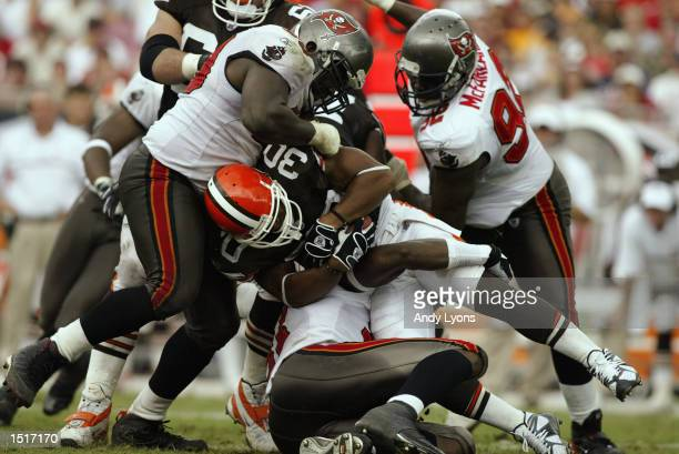 Defensive tackle Warren Sapp and defensive end Simeon Rice of the Tampa Bay Buccaneers tackle running back Jamel White of the Cleveland Browns during...