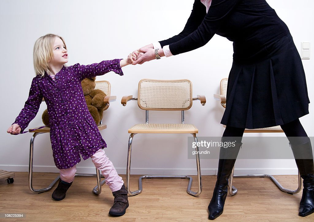 Defiant Little Girl Resisting Mother in Waiting Room