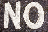 The word 'No' painted in capital letters on a dirty road surface.