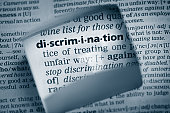 "The Dictionary definition of the word ""discrimination"" photo taken through magnifying glass from a page of a dictionary with selective focus."