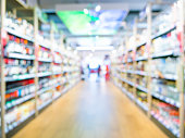 Defocused blur of supermarket aisle of alcohol department. Blur background with bokeh. Defocused image
