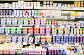 Defocused blur of yogurt on shelves in a supermarket