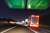 Defocused blurred motion of semi truck speeding on highway under street signs - Night traffic and transport logistic concept with semitruck container driving on speedway - Bokeh and tilted composition