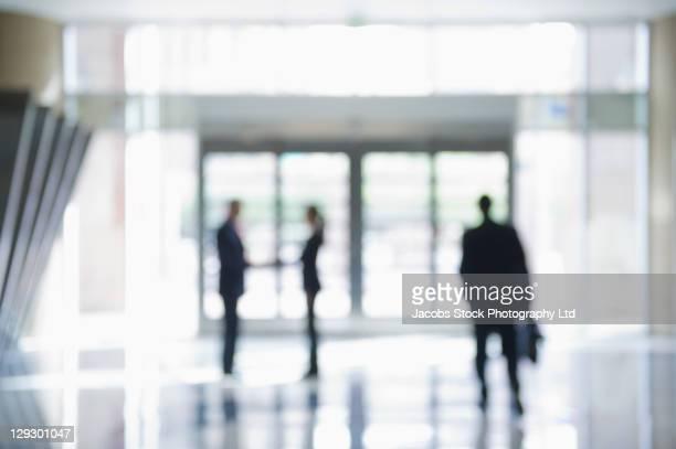 Defocused businesspeople in office lobby
