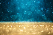 Abstract defocused gold and blue glitter background with copy space