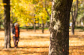 Defocused grandmother walking in public park, natural bokeh background. Abstract blur image of walkway in the park