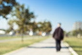 Defocused grandparent walk on the sidewalk. Blurry focus scene