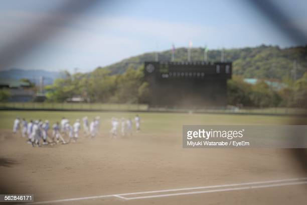 Defocused Image Of People Playing Baseball On Field