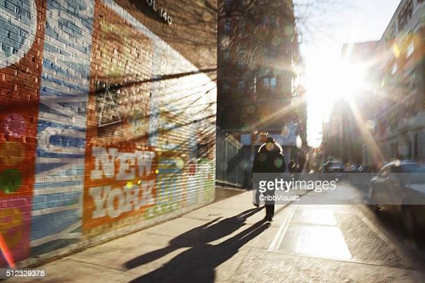 Defocused image of sun rising down New York City backstreet