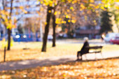 Defocused senior woman sitting on the bench in public park. Abstract blur image of walkway in the park