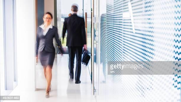 白黒写真のビジネス人々徒歩での現代的なオフィスの廊下