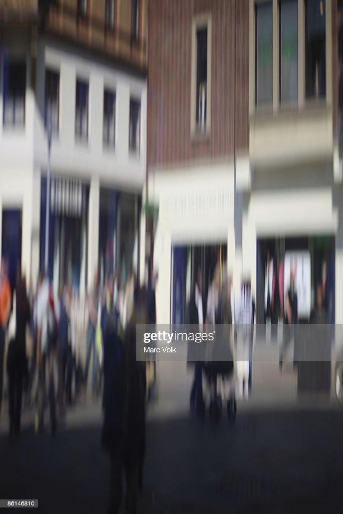 Defocused street scene with people walking