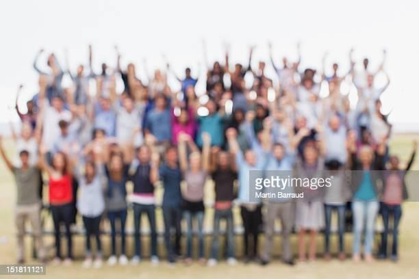 Defocused view of people with arms raised