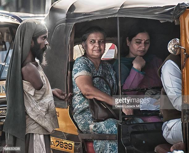 CONTENT] deformed beggar at tuc tuc embarrassed passengers Mumbai near JUHU INDIA