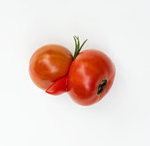 Two red tomatoes grown together with third appendage.
