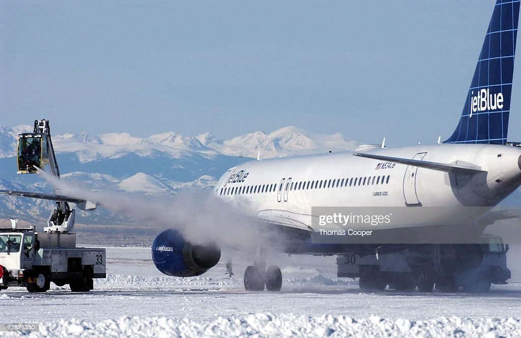 DeIcing crews remove snow and ice from a plane that has been grounded due to a recent blizzard at Denver International Airport December 22 2006 in...