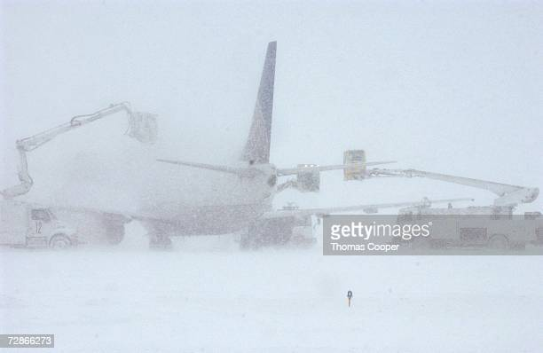 DeIcing crews try to get a Continental Airlines plane clear of snow and ice at Denver International Airport December 20 2006 in Denver Colorado Heavy...