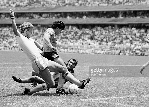 Deigo Maradona of Argentina goes past Terry Butcher and goalkeeper Peter Shilton of England as he scores Argentina's second goal during a World Cup...