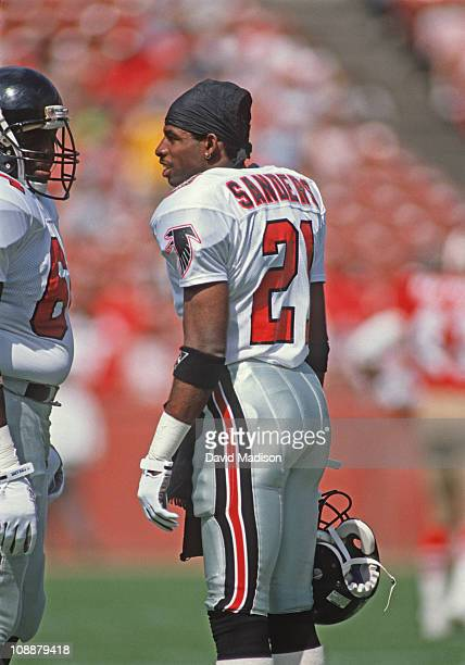 Deion Sanders of the Atlanta Falcons talks to teammate Jamie Dukes before a National Football League game against the San Francisco 49ers played at...