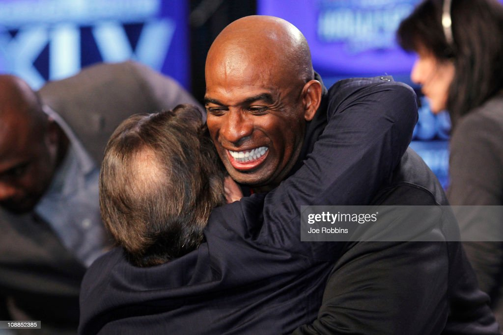 Deion Sanders receives a hug from former coach Steve Mariucci after being named into the 2011 Pro Football Hall of Fame class during an announcement at the Super Bowl XLV media center on February 5, 2011 in Dallas, Texas.
