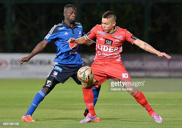 Deiver Machado of Millonarios struggles for the ball with Harold Rivera of Patriotas FC during a match between Patriotas FC and Millonarios as part...