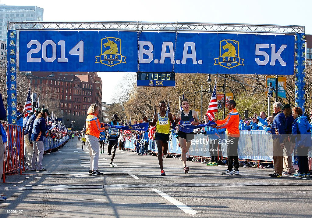 Dejan Gebremeskel of Ethopia edges out Ben True of the United States at the finish line of the 2014 B.A.A. 5K on April 19, 2014 in Boston, Massachusetts.